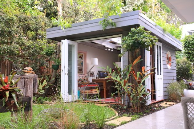 Grey Shed in a lush garden field backyard. It has double doors and looks like a creative space for someone to work in.